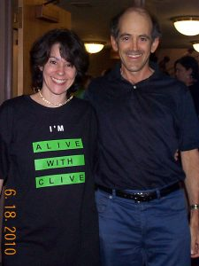 "Holly Yee, the first person in the world to be seen in an ""I'm Alive with Clive"" T-shirt, and Clive Swersky"