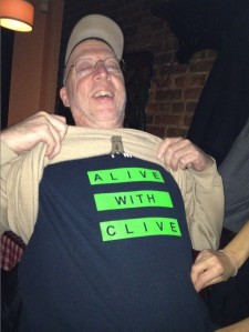 "Robert Randall, lifting his sweater to reveal his ""I'm Alive with Clive"" T-shirt"