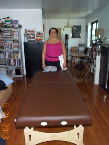 LIcensed Massage Therapist, Kathy Branch, with her massage table